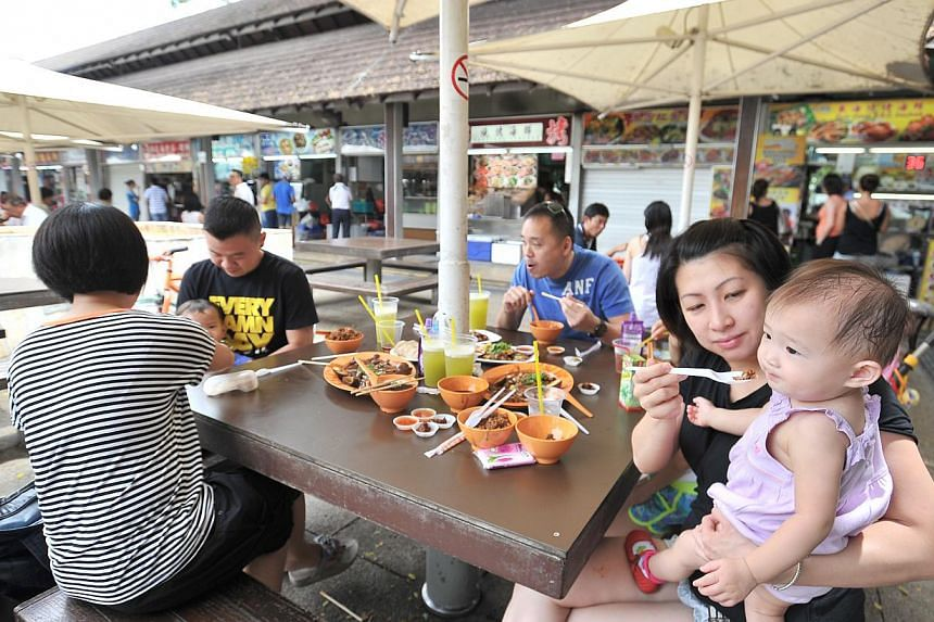 Homemaker Mrs Cindy Tan, 36, (extreme right) feeding her daughter Chenin Tan, 1, at East Coast Lagoon Food Village on Aug 11 2013.-- PHOTOS: LIM YAOHUI FOR THE STRAITS TIMES