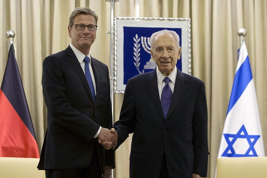 Israel's President Shimon Peres (right), shakes hands with German Foreign Minister Guido Westerwelle during their meeting at the president's residence in Jerusalem, on Sunday, Aug 11, 2013. Westerwelle met Sunday with Israeli officials on a visit to
