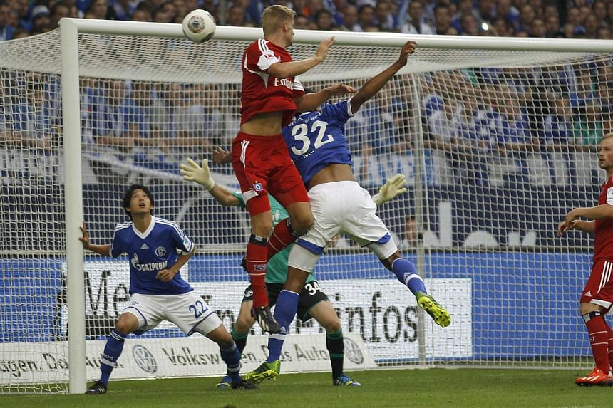 Hamburg SV's Lasse Sobiech (centre) scores a goal against Schalke 04 during the German first division Bundesliga soccer match in Gelsenkirchen on Aug 11, 2013. Schalke 04 and Hamburg shared the points in a 3-3 thriller on Sunday as new-signings grabb