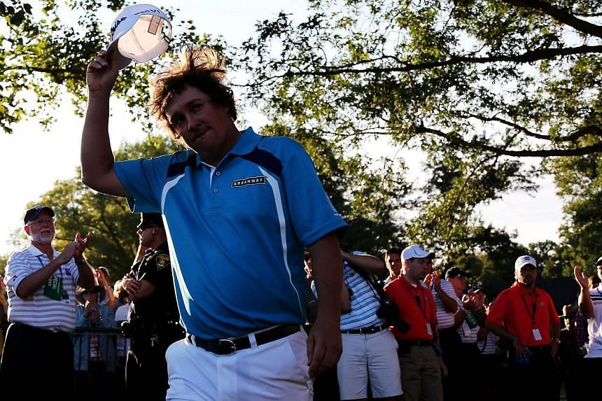 Jason Dufner of the United States walks to the 18th green for the trophy presentation after his two-stroke victory at the 95th PGA Championship at Oak Hill Country Club on Aug 11, 2013 in Rochester, New York. -- PHOTO: AFP