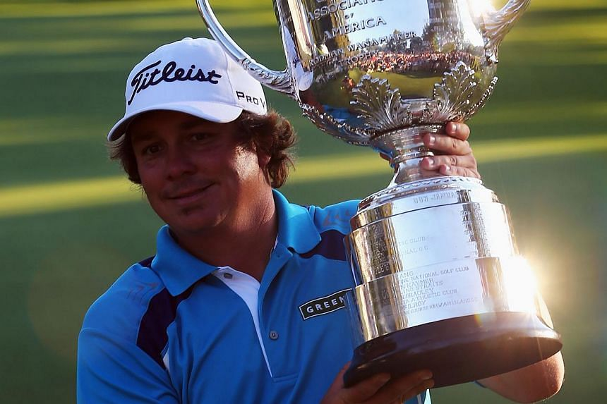 Jason Dufner of the United States celebrates with the Wanamaker Trophy after his two-stroke victory at the 95th PGA Championship at Oak Hill Country Club on Aug 11, 2013 in Rochester, New York. -- PHOTO: AFP
