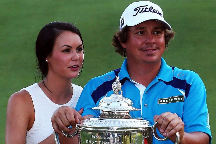 Jason Dufner of the United States and his wife Amanda pose with the Wanamaker Trophy on the 18th green after his two-stroke victory at the 95th PGA Championship at Oak Hill Country Club on Aug 11, 2013 in Rochester, New York. -- PHOTO: AFP