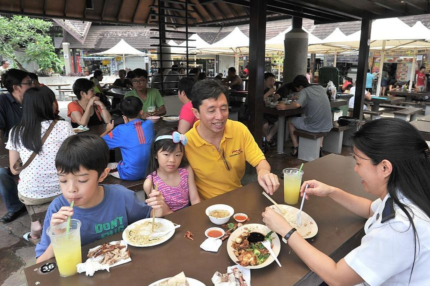 Mr Peter Khoo (in yellow), 48, enjoying a meal at East Coast Lagoon Food Village with his wife, Janice, and children. The social work manager and his family visit the food centre about once a month. -- PHOTOS: LIM YAOHUI FOR THE STRAITS TIMES