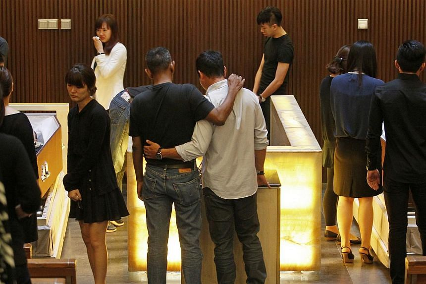 Friends and family attend the funeral service of the Korean family killed in a car crash on the CTE at the Mandai Crematorium on Aug 12, 2013. -- ST PHOTO: MARK CHEONG