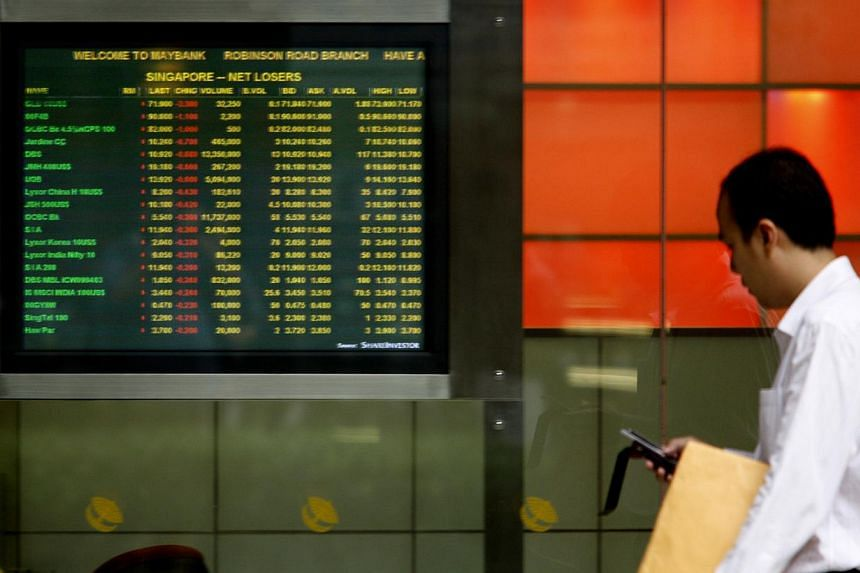 A man walks past a stock market board. BLUE chips in Singapore inched upwards on Monday amid mixed performances in regional markets. -- ST FILE PHOTO: BRYAN VAN DER BEEK