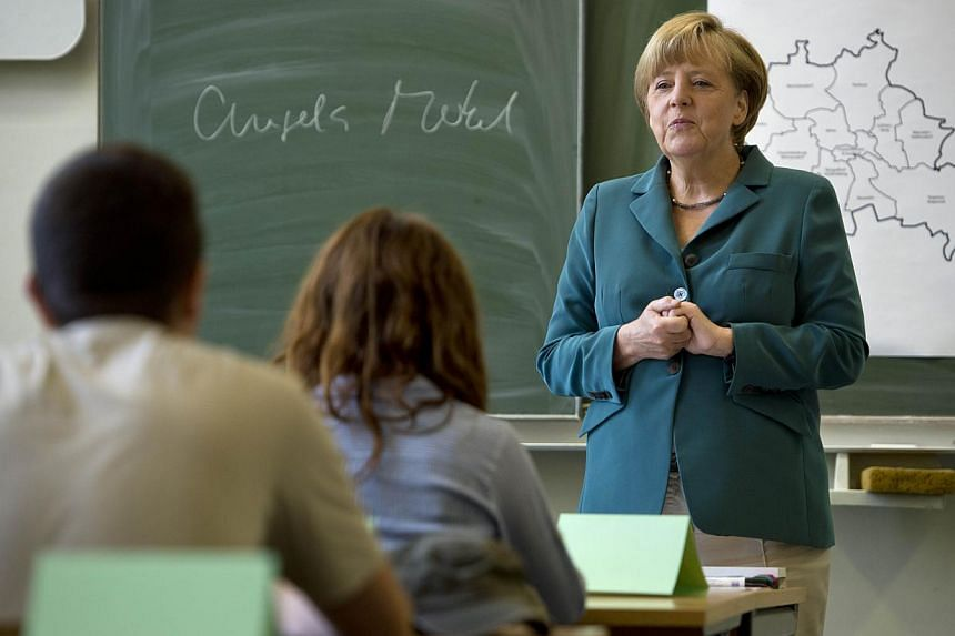 German Chancellor Angela Merkel, campaigning for a third term, filled in as a school history teacher on Tuesday on the 52nd anniversary of the building of the Berlin Wall. -- PHOTO: AFP