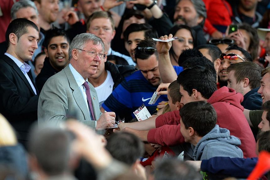 Manchester United's Scottish former manager Alex Ferguson signs autographs for fans during a Charity football match between Manchester United Legends and Real Madrid Legends at Old Trafford in Manchester, north-west England on June 2, 2013. After a c