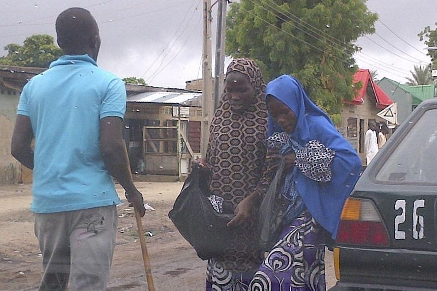 """Two women are seen through a car windshield as they approach a member of vigilante groups popularly called the """"civilian JTF"""" armed with a stick in Mafoni village, Borno state on August 6, 2013. Suspected Islamist extremists have stormed a mosque and"""