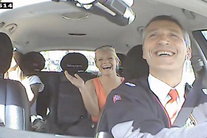This video grab taken on August 11, 2013 from a video made available by the Norwegian Labour Party shows Norwegian Prime Minister Jens Stoltenberg (right) acting as a taxi driver in Oslo, Norway as a part of the election campaign for the Norwegian La
