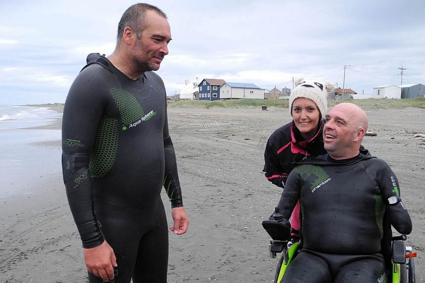 A file picture taken on August 11, 2012 shows French swimmer Philippe Croizon, four-member amputee (right) speaking with his friend, swimmer Arnaud Chassery (left), on a beach in Wales, Alaska. Croizon, known for his feats of swimming and diving, sai