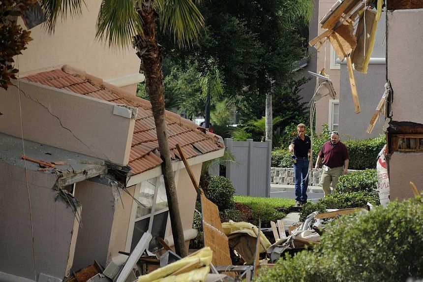 A building sits partially collapsed over a sinkhole at Summer Bay Resort near Disney World on Aug 12, 2013 in Clermont, Florida. The 40 to 60 foot sinkhole opened up under the resort building reportedly begining late Aug 11 into early Aug 12. There w