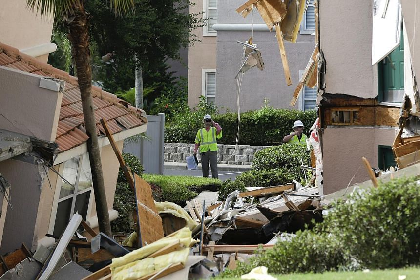 Inspectors look over damage to buildings caused by a sinkhole 40 to 50 feet in diameter at the Summer Bay Resort, on Monday, Aug 12, 2013, in Clermont, Florida. Lake County Fire Rescue Battalion Chief Tony Cuellar says about 30 per cent of the three-