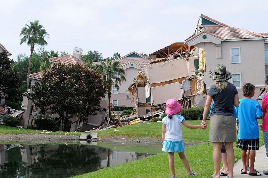 People look at a partially collapsed building over a sinkhole at Summer Bay Resort near Disney World on Aug 12, 2013 in Clermont, Florida. Dozens of guests at a Florida resort near Walt Disney World were safely evacuated in the middle of the night on