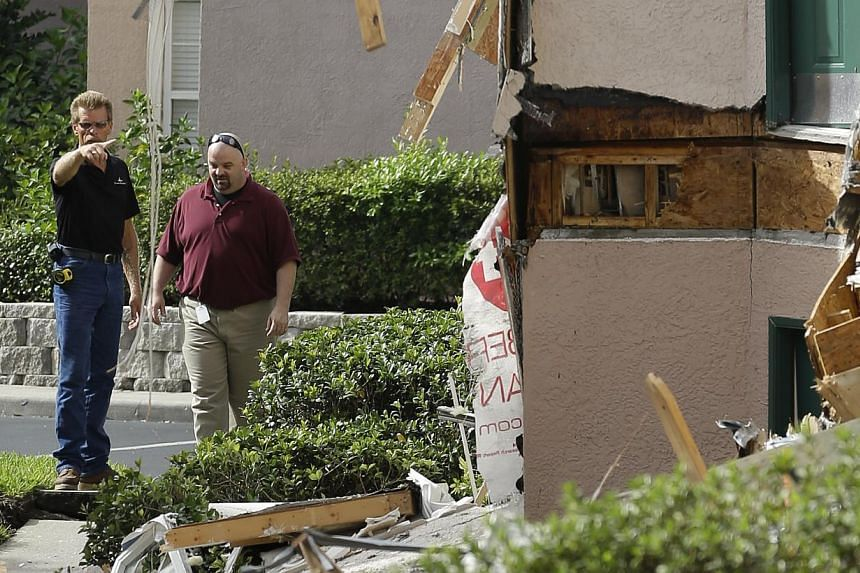 Inspectors look over damage to three buildings caused by a sinkhole 40 to 50 feet in diameter at the Summer Bay Resort, on Monday, Aug 12, 2013, in Clermont, Florida. Part of a building collapsed and another section was sinking. -- PHOTO: AP