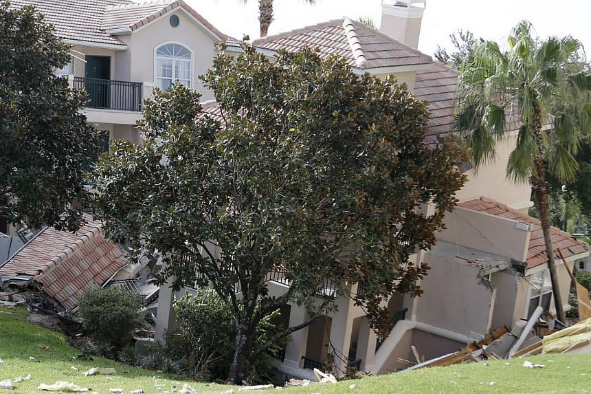 A portion of a building rests in a sinkhole on Monday, Aug 12, 2013 in Clermont, Florida. The sinkhole, 40 to 50 feet in diameter, opened up overnight and damaged three buildings at the Summer Bay Resort. -- PHOTO: AP