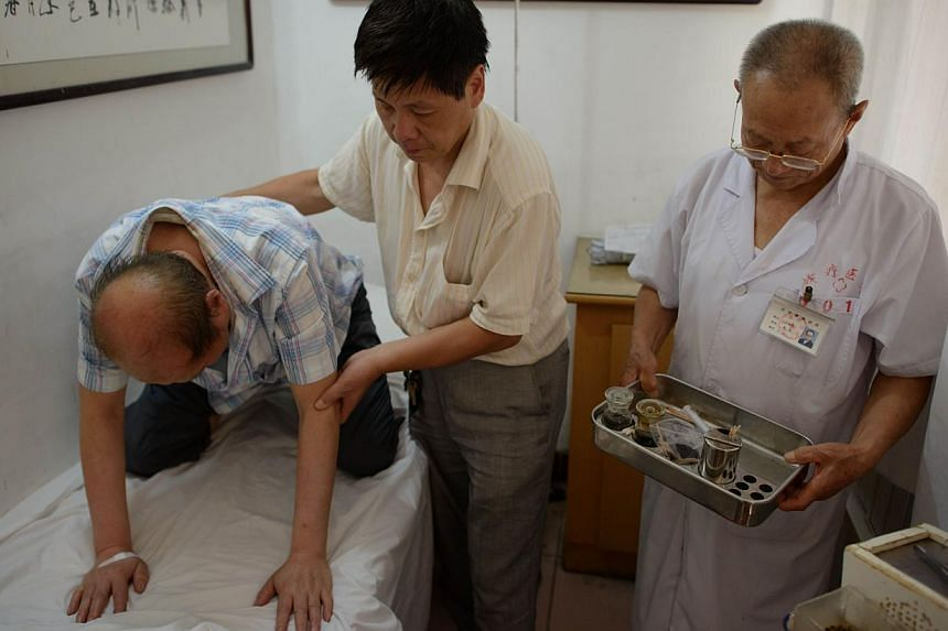 A patient suffering from cancer (left) rests after receiving bee stings from a doctor of traditional Chinese medicine (right) at a clinic on the outskirts of Beijing on Aug 2, 2013. Patients in China are swarming to acupuncture clinics to be given be