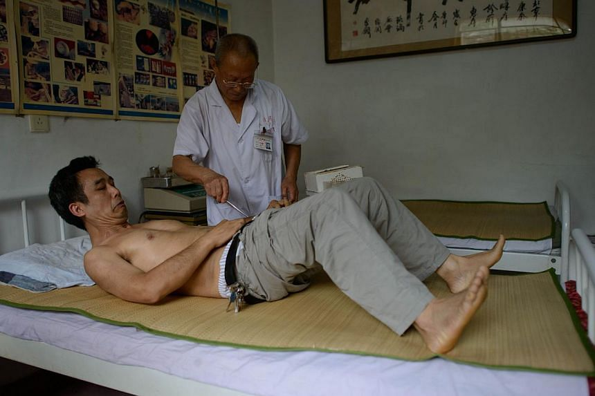 A patient receives bee stings administered by a doctor of traditional Chinese medicine (top) at a clinic on the outskirts of Beijing on Aug 2, 2013. Patients in China are swarming to acupuncture clinics to be given bee stings to treat or ward off lif