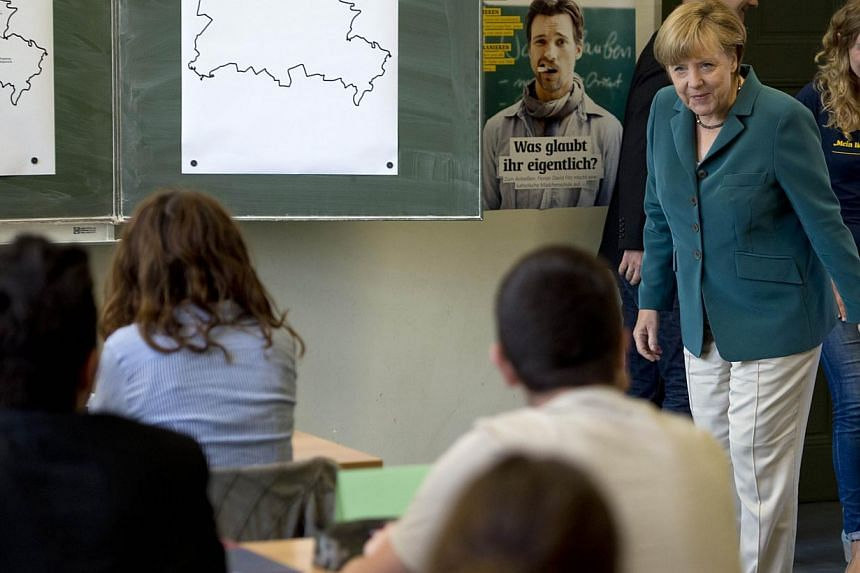German Chancellor Angela Merkel bows as she enters the classroom to lecture on the building of the Berlin Wall on Aug 13, 1961, to a 12th grade class during her visit to the Heinrich Schliemann Gymnasium, secondary school in Berlin, Germany on Aug 13