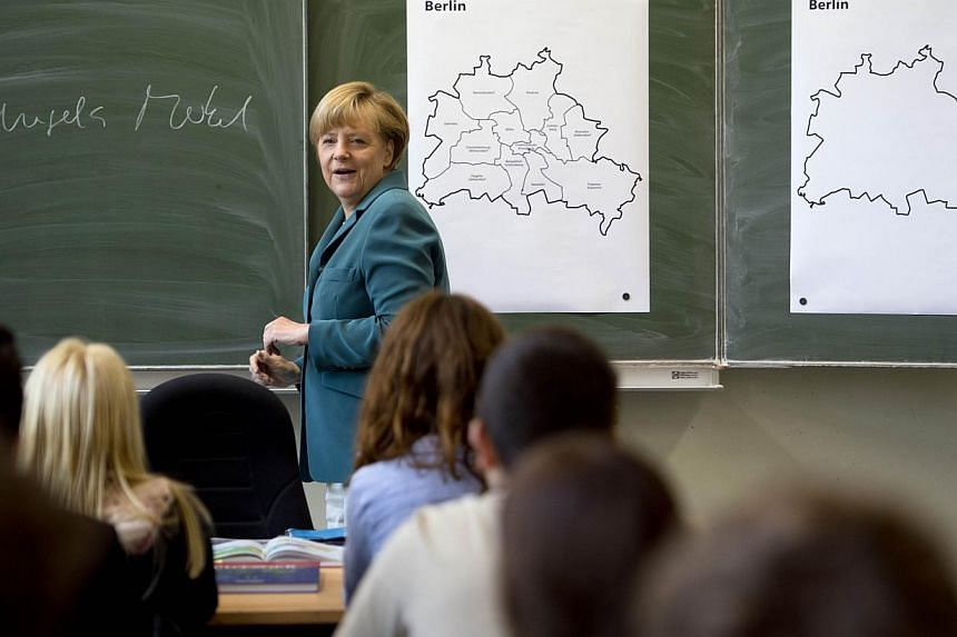 German Chancellor Angela Merkel writes her name on the black board and starts her lecture on the building of the Berlin wall on Aug 13,1961, to a 12th grade class during her visit to the Heinrich Schliemann Gymnasium, secondary school in Berlin, Germ