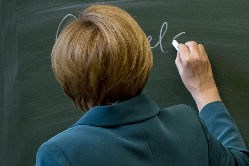 German Chancellor Angela Merkel writes her name on the black board before starting her lecture on the building of the Berlin wall on Aug 13,1961, to a 12th grade class during her visit to the Heinrich Schliemann Gymnasium, secondary school in Berlin,