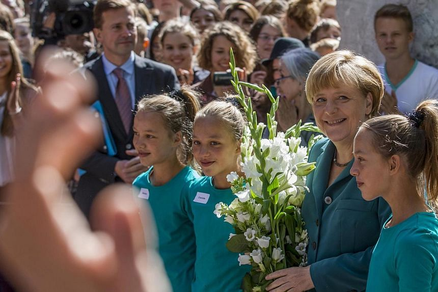 German Chancellor Angela Merkel (2nd right) poses with 6th graders, identical triplets Marlene (left), Charlotte (2nd left) and Elizabeth, after arriving at the Heinz Schliemann grammar school in Berlin, Aug 13, 2013. Ms Merkel on Tuesday delivered a