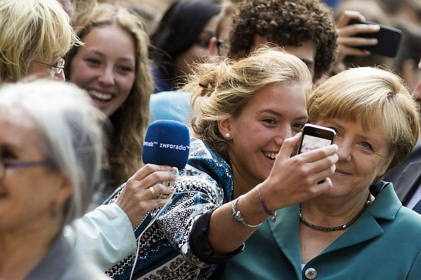 German Chancellor Angela Merkel (right) has her picture taken with a pupil as she arrives for a visit to the Heinz Schliemann grammar school in Berlin, Aug 13, 2013. Ms Merkel on Tuesday delivered a guest history lecture on the erection of the Berlin