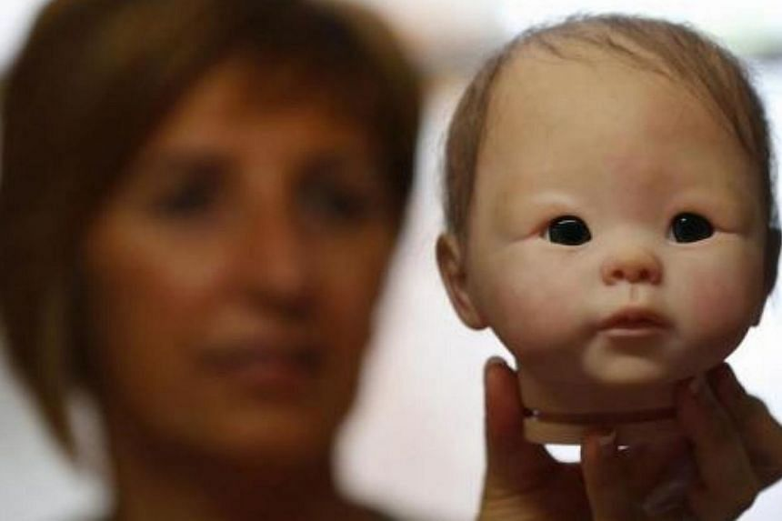 """Belgian artist Beatrice Van Landeghem looks at the back of the head of one of her life-like """"Reborn Baby"""" dolls at her workshop called La nurserie des Tis Lous De Bea in La Louviere, southern Belgium on Aug 8, 2013.-- PHOTO: REUTERS"""