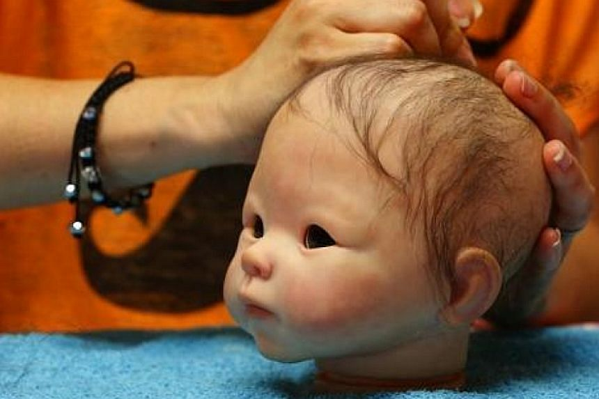 "Belgian artist Beatrice Van Landeghem uses a needle to attach hair to the head of one of her life-like ""Reborn Baby"" dolls at her workshop called La nurserie des Tis Lous De Bea"" in La Louviere, southern Belgium on Aug 8, 2013. -- PHOTO: REUTERS"