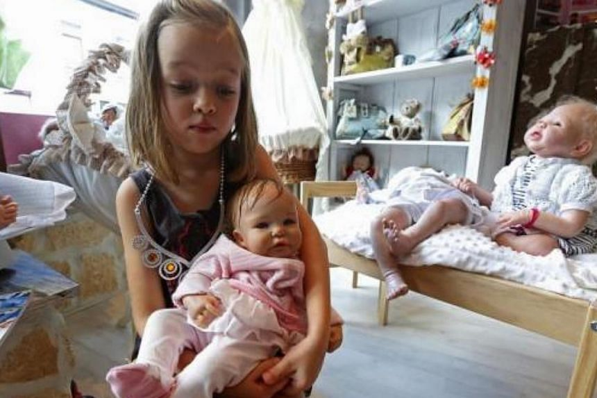 "Tyssia, six, daughter of Belgian artist Beatrice Van Landeghem, poses with her ""Reborn Baby"" doll named Betty Lou at her mother's workshop called La nurserie des Tis Lous De Bea in La Louviere, southern Belgium on Aug 8, 2013. -- PHOTO: REUTERS"