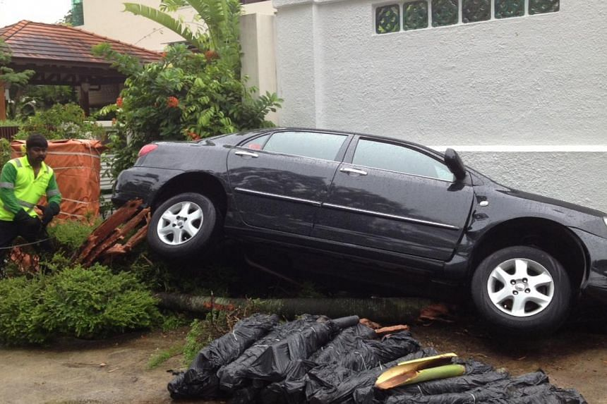 A car was found turned on its side in a drain outside a home on 103 Sunset Way around 10.30am on Tuesday morning. -- ST PHOTO: MALCOLM MCLEOD