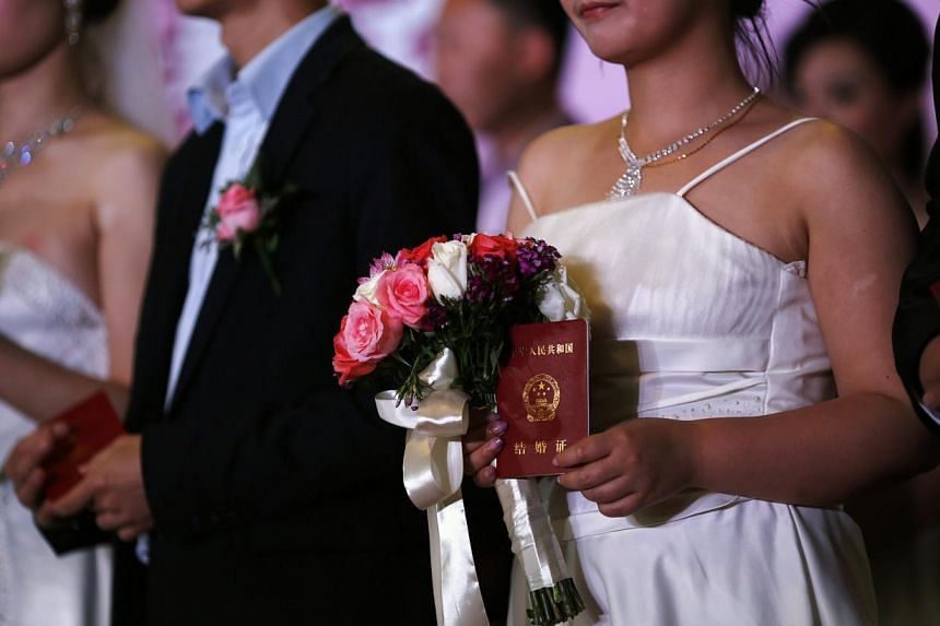 """A woman holds her marriage certificate as couples participate in a staged mass wedding, organised as part of a matchmaking event to inspire singles to get married, in a suburban area of Shanghai on May 18, 2013. As couples celebrate the """"Qixi"""" festiv"""