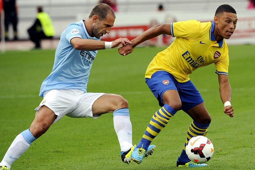 Manchester City's Pablo Zabaleta (left) fights for the ball with Arsenal's Alex Oxlade-Chamberlain during the two English Premier League teams' friendly football match at the Helsinki Olympic Stadium in Helsinki on Saturday, Aug 10, 2013. It is still
