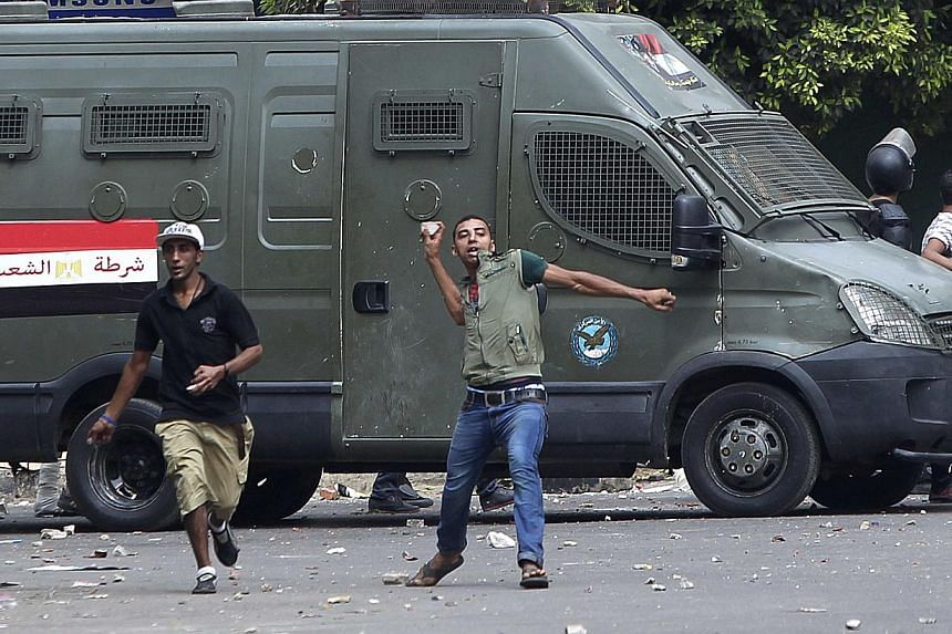 A local resident throws stones towards supporters of ousted President Mohamed Mursi during clashes in central Cairo on Tuesday, Aug 13, 2013. Clashes broke out in central Cairo on Tuesday when supporters of ousted President Mohamed Mursi came under a