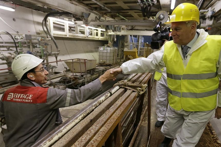 French Prime Minister Jean-Marc Ayrault shakes hands with an employee of Eiffage TP during a visit of a tunnel digging site, part of a future tramway line, in Velizy-Villacoublay, near Paris on Wednesday, Aug 13, 2013. France's government is mulling