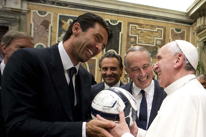 Pope Francis receives a football as gift from Italy's goalkeeper Gianluigi Buffon (left) during a private audience at the Vatican on Aug 13, 2013. Pope Francis joked with Italy and Argentina players on the eve of a friendly football match in Rome on