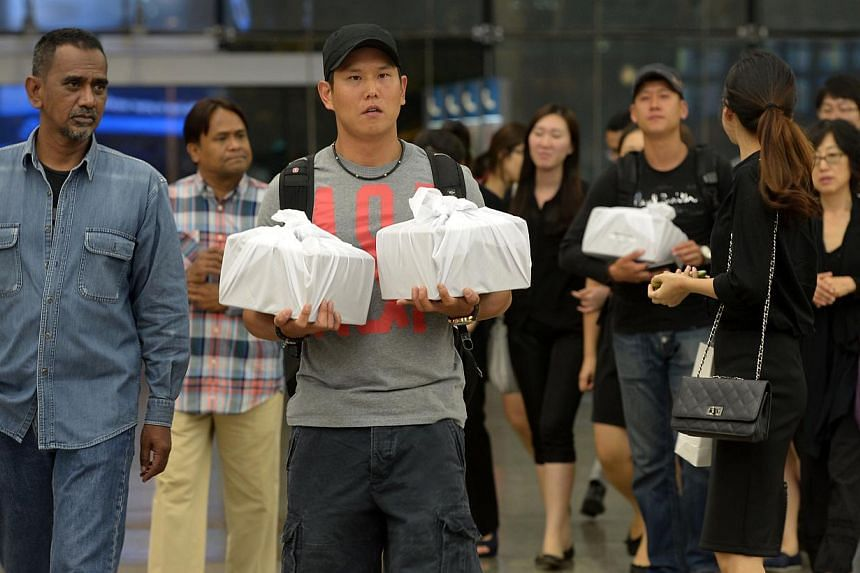 Mr Song Seoung Hwan (left, foreground) and his brother Jihwan carrying the urns of their parents and sister Jamie at Changi Airport. Mr Amron's father Ayoub Ahmat (extreme left) and their families and friends sent them off. -- PHOTOS: NG SOR LUAN,