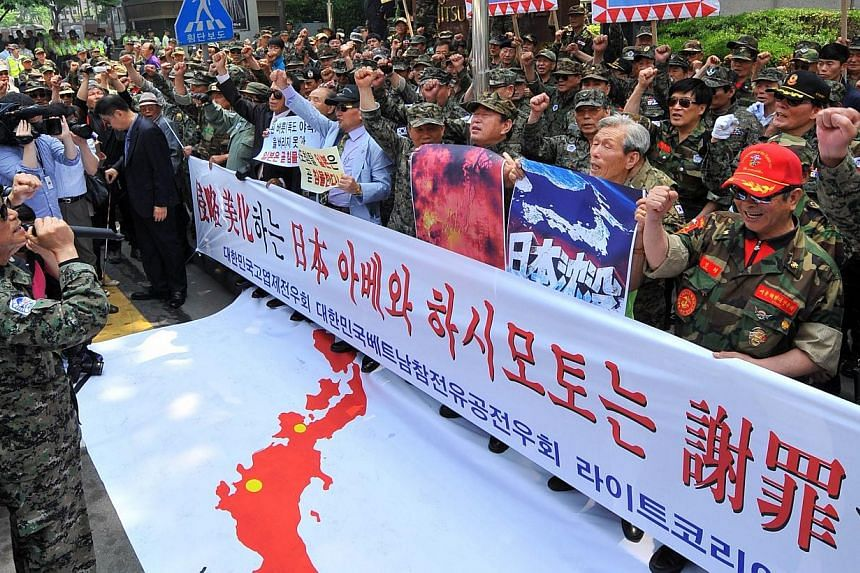 Hundreds of South Korean veterans shout anti-Japan slogans during a rally outside the Japanese embassy in Seoul on Thursday, May 23, 2013. South Korea on Tuesday, Aug 13, 2013, warned Japanese politicians against visiting a controversial war shrine o