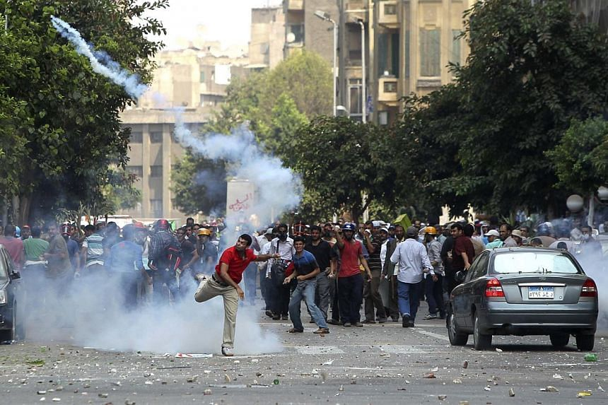 A supporter of ousted President Mohamed Mursi throws a tear gas canister back towards the police during clashes in central Cairo, Aug 13, 2013. Egyptian police fired tear gas to break up clashes between supporters of ousted president Mohamed Mursi an