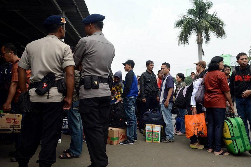 Policemen stand at Senen Station in Jakarta on August 6, 2013 as thousands of Indonesians return home to their villages in preparation for Eid al-Fitr celebrations as the Islamic holy month enters its final week. Crimes involving hypnotists tend to s