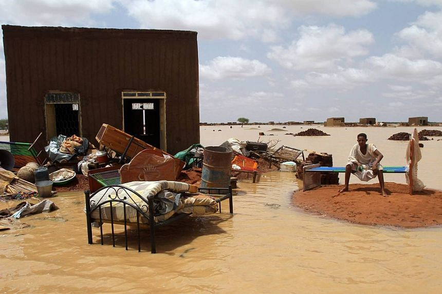 A Sudanese man sits next to his house in a flooded street on the outskirts of the capital Khartoum on Aug 10, 2013. The number of people affected by this month's flooding in Sudan has climbed to around 150,000 and is expected to rise further, the Uni