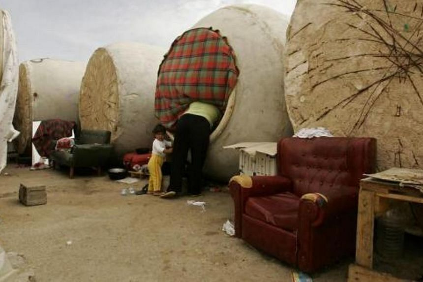 A Bulgarian woman looks inside her wine vat home in Socuellamos, central Spain on Oct 2, 2007. About 40 people living in this makeshift camp are ethnic Turks from Bulgaria who came to the vineyards of Socuellamos to pick grapes during the six-week an