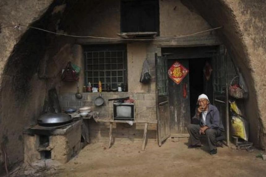 A man sits as he smokes at the door of his cave-room in Yuncheng, Shanxi province, China on Aug 7, 2010. -- FILE PHOTO: REUTERS