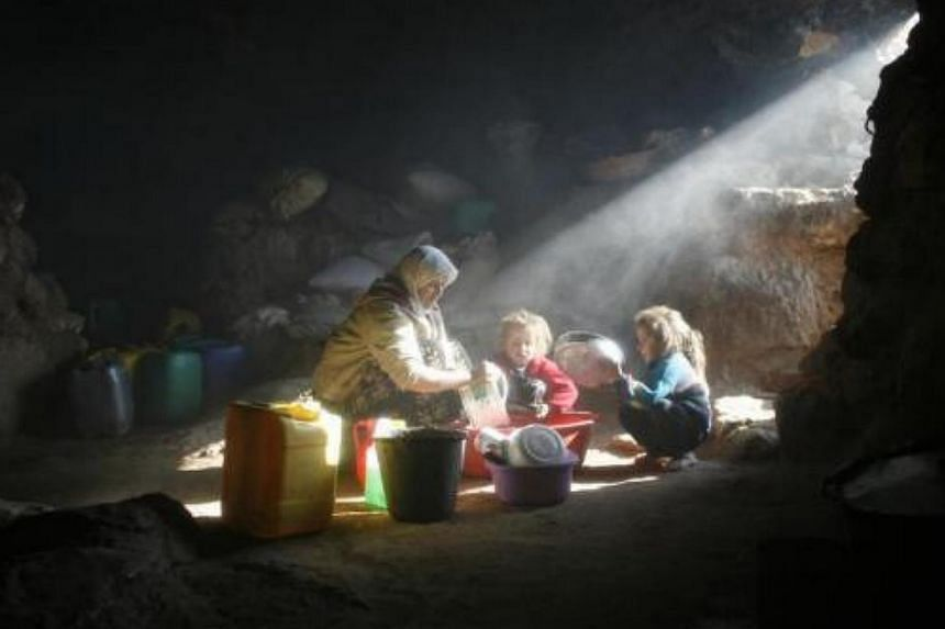 Palestinian Halimeh Saleem (left) washes dishes at her cave home in the northern Negev Desert, near the West Bank city of Hebron on Jan 17, 2007. -- FILE PHOTO: REUTERS