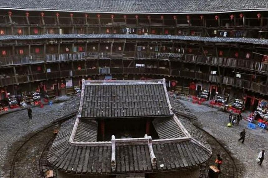 Visitors walk inside a nearly 700-year-old Fujian Tulou in Nanjing county, Fujian province, China on Nov 19, 2012. The earthen Tulou buildings, which set up enclosed walls to defend against outside dangers, have served the Hakka people since 11th cen