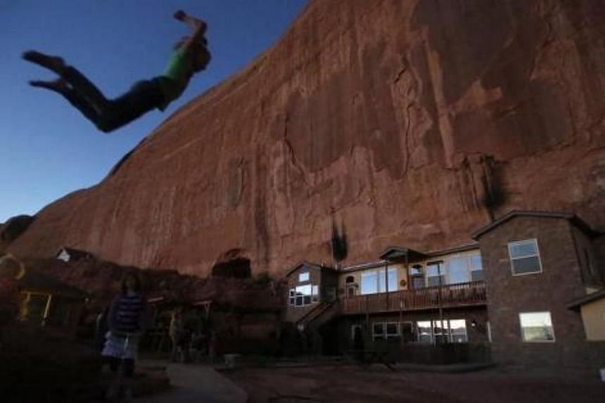 """Girls play on a trampoline near a home blasted from a rock wall at the Rockland Ranch community outside Moab, Utah on Nov 2, 2012. The """"Rock"""" as it is referred to by the approximately 100 people living there in about 15 families, was founded about 35"""