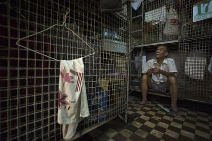 Mr Kong Siu-kau waits for dinner in a small cage in Hong Kong's Tai Kok Tsui district on July 16, 2008. In older districts like Tai Kok Tsui, hundreds of elderly men still reside in caged cubicles in cramped, old tenement flats which house up to 12 i