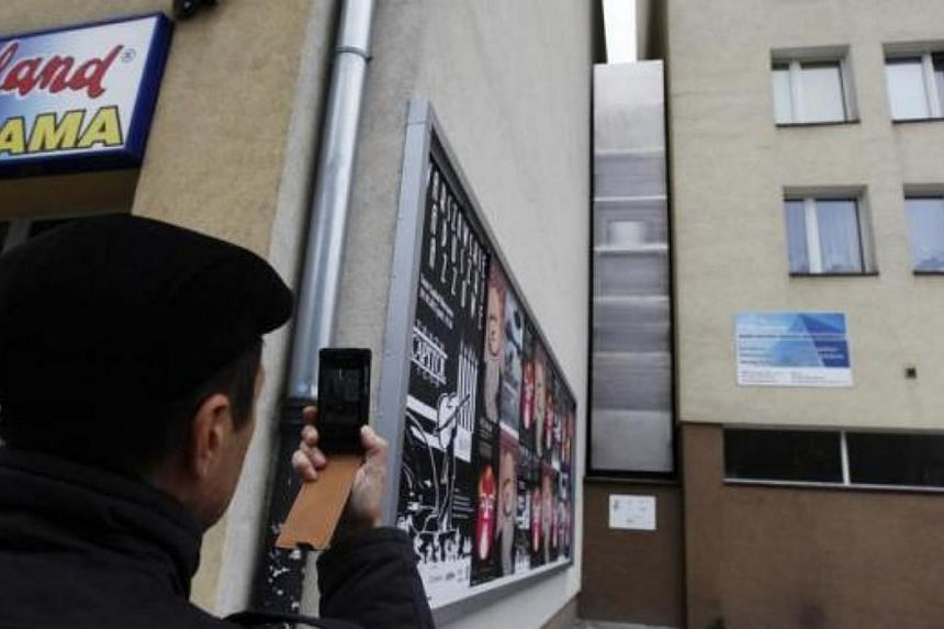 A man takes a picture of the one of the world's narrowest buildings, built as an artistic installation wedged between two existing buildings, in Warsaw on Oct 23, 2012. A building just 92cm wide as its narrowest point was opened in Warsaw on O