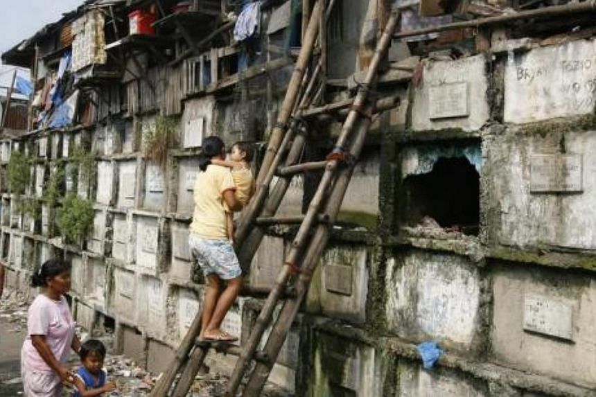 Residents climb into their houses atop gravestones inside a cemetery in Manila on Oct 21, 2008. Many poor urban dwellers make their homes in public cemeteries, converting abandoned tombs and mausoleums into houses. -- FILE PHOTO: REUTERS