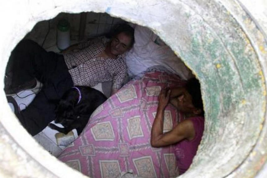 Mr Miguel Restrepo (left), 62, and wife Maria Garcia are seen from their sewer home in Medellin Dec 4, 2012. The former drug addict has been living in an abandoned sewer with his wife and dog Blackie for 22 years. Their home, which is fitted with a k