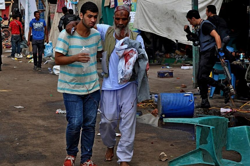 A supporter of ousted Islamist President Mohammed Mursi helps another walk as Egyptian security forces clear a sit-in camp set up by near Cairo University in Cairo's Giza district, Egypt, Wednesday, Aug 14, 2013. -- PHOTO: AP